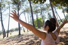 Mujer que se coloca con los brazos extendidos en el parque Foto de archivo
