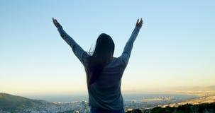 Mujer que se coloca con los brazos extendidos encima de la montaña 4k metrajes