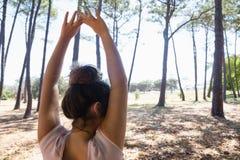 Mujer que se coloca con los brazos para arriba en el parque Foto de archivo