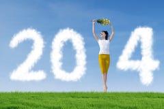 Mujer que se coloca con 2014 nubes del Año Nuevo Fotos de archivo