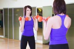 Mujer que se coloca con pesas de gimnasia en un gimnasio que mira en sí misma en un espejo Fotos de archivo libres de regalías