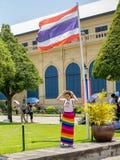 Mujer que se coloca debajo de bandera tailandesa Fotos de archivo libres de regalías