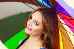 Mujer que se coloca debajo del paraguas colorido del arco iris Imágenes de archivo libres de regalías