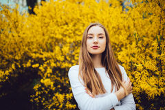 Mujer que se coloca delante de árbol floreciente amarillo en calle de la ciudad Foto de archivo