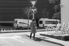 Mujer que se coloca delante de una señal de tráfico y que se pregunta adonde ir Imagen de archivo libre de regalías