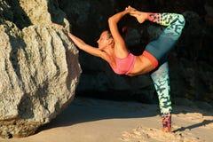Mujer que se coloca en actitud de la yoga en roca de la playa del mar Imagen de archivo libre de regalías