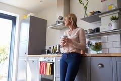 Mujer que se coloca en cocina con la bebida caliente foto de archivo libre de regalías