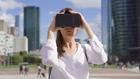 Mujer que se coloca en distrito financiero céntrico usando los vidrios de la realidad virtual Rascacielos en fondo almacen de metraje de vídeo