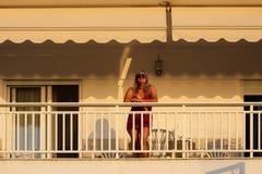 Mujer que se coloca en el balcón temprano por la mañana durante el Su Fotografía de archivo libre de regalías