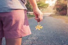 Mujer que se coloca en el camino concreto en el campo por la mañana Ella que sostiene la flor amarilla hermosa en su mano imagenes de archivo