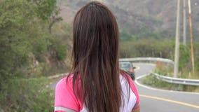 Mujer que se coloca en el camino curvado de la montaña almacen de metraje de vídeo