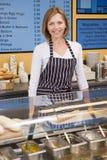 Mujer que se coloca en el contador en la sonrisa del restaurante Imágenes de archivo libres de regalías