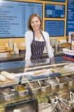Mujer que se coloca en el contador en la sonrisa del restaurante fotos de archivo