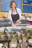 Mujer que se coloca en el contador en la sonrisa del restaurante Fotos de archivo libres de regalías