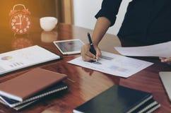 Mujer que se coloca en el escritorio y el documento de trabajo de la escritura Fotos de archivo libres de regalías