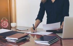 Mujer que se coloca en el escritorio y el documento de trabajo de la escritura Foto de archivo
