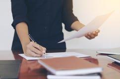 Mujer que se coloca en el escritorio y el documento de trabajo de la escritura Imágenes de archivo libres de regalías