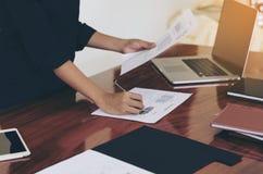 Mujer que se coloca en el escritorio y el documento de trabajo de la escritura Imagenes de archivo