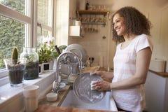Mujer que se coloca en el fregadero de cocina que se lava para arriba Imagenes de archivo