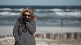 Mujer que se coloca en el océano en tiempo de congelación foto de archivo