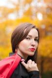 Mujer que se coloca en el parque en otoño Foto de archivo