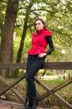 Mujer que se coloca en el parque en otoño Fotografía de archivo libre de regalías