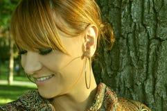 Mujer que se coloca en el parque y la sonrisa Fotografía de archivo libre de regalías