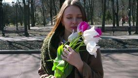 Mujer que se coloca en el parque y que sostiene el ramo de blanco almacen de video