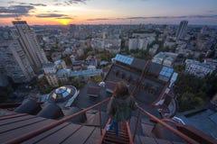 Mujer que se coloca en el tejado en el edificio moderno en Kiev, Ucrania Foto de archivo