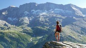 Mujer que se coloca en el top de la montaña en paisaje rocoso de la mucha altitud con el glaciar y el pico en el fondo Aventuras  almacen de metraje de vídeo