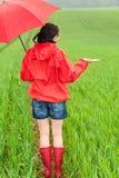 Mujer que se coloca en impermeable y con el paraguas Fotos de archivo libres de regalías