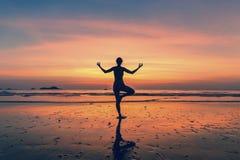 Mujer que se coloca en la actitud de la yoga en la playa durante puesta del sol fantástica Foto de archivo libre de regalías