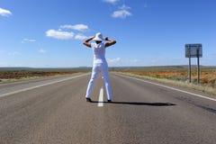 Mujer que se coloca en la carretera Imagen de archivo
