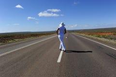 Mujer que se coloca en la carretera Fotografía de archivo