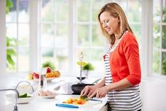 Mujer que se coloca en la comida preparada contraria en cocina Foto de archivo libre de regalías
