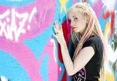 mujer que se coloca en la pared del graffitti Fotografía de archivo