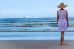 Mujer que se coloca en la playa Imagenes de archivo