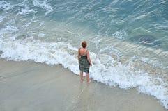 Mujer que se coloca en la playa arenosa Fotos de archivo libres de regalías