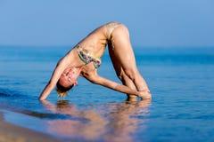 Mujer que se coloca en la playa que hace yoga Fotografía de archivo libre de regalías
