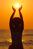 Mujer que se coloca en la playa, sosteniendo el sol en manos Fotos de archivo