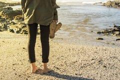 Mujer que se coloca en la playa y que mira hacia fuera al mar fotos de archivo libres de regalías