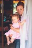 Mujer que se coloca en la puerta del patio con su pequeña hija Fotos de archivo libres de regalías