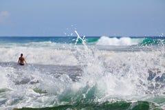 Mujer que se coloca en la resaca del mar con las ondas grandes Imagenes de archivo