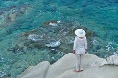 Mujer que se coloca en la roca cerca del mar Fotografía de archivo libre de regalías