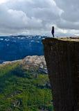 Mujer que se coloca en la roca Preikestolen Noruega del púlpito Foto de archivo libre de regalías