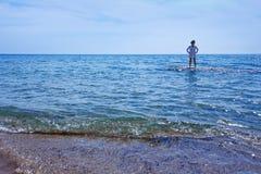 Mujer que se coloca en las aguas poco profundas del mar fotos de archivo libres de regalías