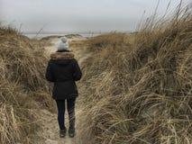Mujer que se coloca en las dunas Imagenes de archivo