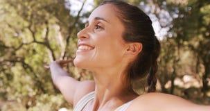 Mujer que se coloca en parque con sus brazos estirados almacen de video