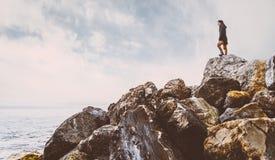 Mujer que se coloca en piedra cerca del mar fotografía de archivo