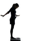 Mujer que se coloca en silueta feliz de la escala del peso Imagen de archivo